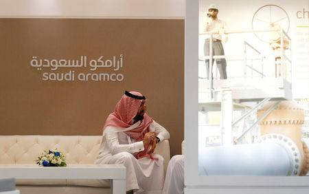 FILE PHOTO: A Saudi Aramco employee sits in the area of its stand at the Middle East Petrotech 2016 in Manama