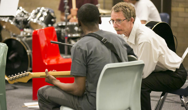 Chicago Symphony Orchestra Bass Dan Armstrong talks to an unidentified inmate during their music performance for inmates as part of the CSO's Citizen Musician program which brings music to a variety of locations including prisons, Sunday, April 14, 2013. (AP Photo/Todd Rosenberg)