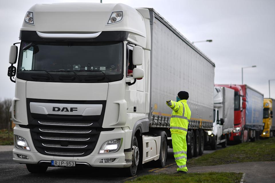 A traffic marshall checks the documents of a freight lorry driver at Waterbrook Park facility in Ashford, south east England on January 15, 2021, as hauliers get used to life under the post-Brexit trade deal. - British companies are struggling with a large amount of red tape as a result of Brexit, with senior government minister Michael Gove recently admitting that there would be