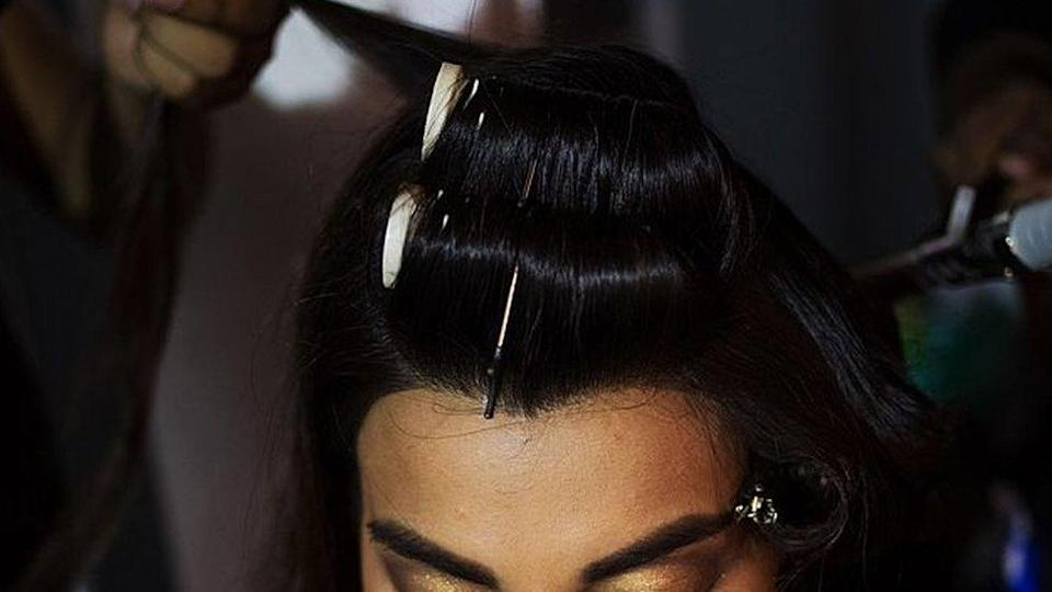 An Indian model sits as she has her hair styled backstage ahead of the Ashima Leena fashion show at Bridal Fashion Week in New Delhi.