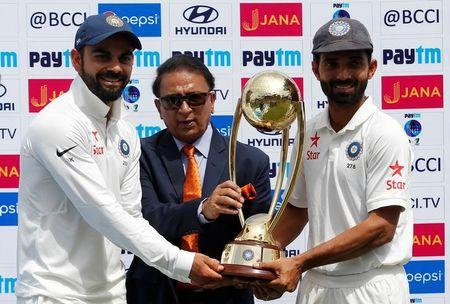 Cricket - India v Australia - Fourth Test cricket match - Himachal Pradesh Cricket Association Stadium, Dharamsala, India - 28/03/17 - India's Virat Kohli (L) and Ajinkya Rahane (R) receive the trophy from the former Indian cricket player Sunil Gavaskar after winning the series. REUTERS/Adnan Abidi