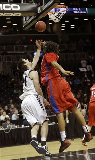 Butler's Andrew Smith, left, throws up a shot past Dayton's Jalen Robinson during the first half of an NCAA college basketball game at the Atlantic 10 Conference tournament in New York, Thursday, March 14, 2013. (AP Photo/Seth Wenig)