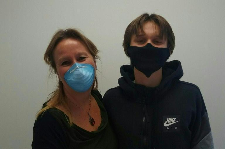 Chicago physician Kathy Tynus and her 17-year-old son Tony wear protective masks during the shelter-in-place mandate in Chicago, Illinois