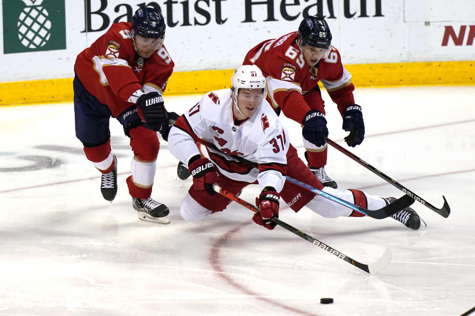 Carolina Hurricanes right wing Andrei Svechnikov (37) passes the puck as Florida Panthers center Sam Bennett (9) and defenseman Markus Nutivaara (65) defend during the second period of an NHL hockey game Thursday, April 22, 2021, in Sunrise, Fla. (AP Photo/Marta Lavandier)