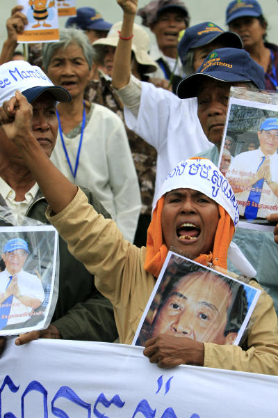Cambodian supporters of Mam Sonando, one of Cambodia's most prominent human rights defenders, protest in front of the Phnom Penh Municipal Court, in Phnom Penh, Cambodia, Monday, Oct. 1, 2012. Some 300 supporters gathered to demand the release of local radio station owner Mam Sonando, who is accused of leading a secession, and has been held in pre-trial detention for almost two months. His verdict is scheduled to be announced at the court on Monday. (AP Photo/Heng Sinith