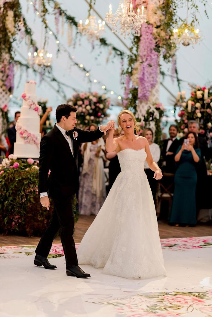 Alex Drummond in a white wedding gown dances with her new husband in a black suit on a dance floor under hanging purple flowers (Courtesy of Ashley Alexander Photography)