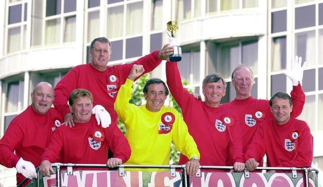 Seven of England's victorious 1966 World Cup winning team celebrate with a replica Jules Rimet trophy