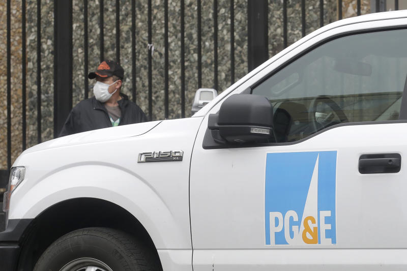FILE - In this April 16, 2020, file photo, a man wearing a mask walks behind a Pacific Gas and Electric truck in San Francisco. Pacific Gas & Electric's proposal to pay $25.5 billion for a series of deadly Northern California wildfires ignited by its equipment faces a last-ditch effort to persuade a judge to reject the plan to get the nation's largest utility out of bankruptcy. (AP Photo/Jeff Chiu, File)