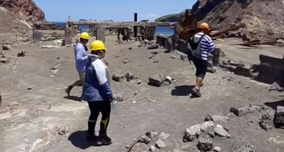 A tour group looks at ruins on White Island, New Zealand.