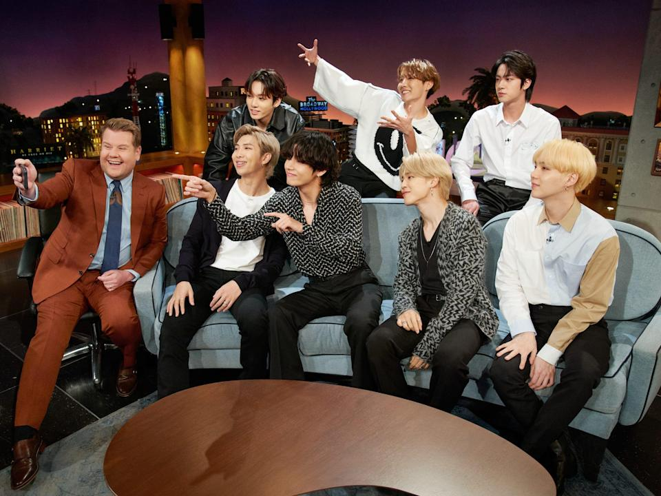 james corden on the set of the late late show taking a selfie with the seven members of bts, sitting on and standing behind a couch