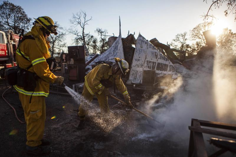 Shasta County firefighters spray water on a home burnt by the Clover Fire in Happy Valley