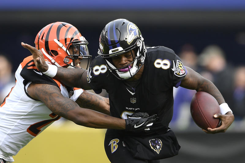 Baltimore Ravens quarterback Lamar Jackson (8) tries to break free from Cincinnati Bengals defensive back Darqueze Dennard as he rushes the ball in the first half of an NFL football game, Sunday, Nov. 18, 2018, in Baltimore. (AP Photo/Nick Wass)