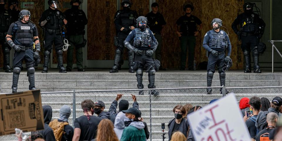 """Portland police officers in riot gear stand outside the Portland Justice Center during protests on May 31, 2020. <p class=""""copyright""""><a href=""""https://www.gettyimages.com/detail/news-photo/heavily-armed-riot-police-stand-on-the-porch-of-the-damaged-news-photo/1216633354?adppopup=true"""" rel=""""nofollow noopener"""" target=""""_blank"""" data-ylk=""""slk:John Rudoff/Anadolu Agency via Getty Images"""" class=""""link rapid-noclick-resp"""">John Rudoff/Anadolu Agency via Getty Images</a></p>"""