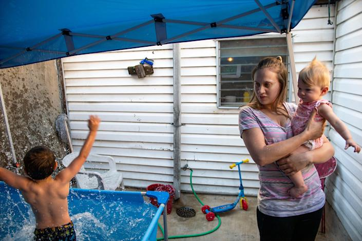 Carmen Aponte-Vincent, 22, holds her daughter Maria Floyd as her son Chase Aponte-Hopely, 6, plays in the pool at home in Philadelphia, Pa. on Friday, June 4, 2021.