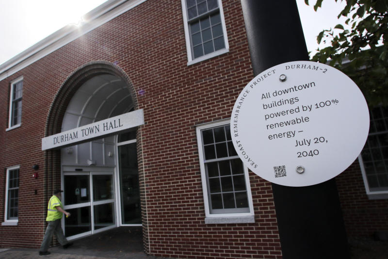 A sign, part of a public design installation by artist Thomas Starr, is displayed on a light pole outside town hall in Durham, N.H., Wednesday, Oct. 16, 2019. Starr, a graphic and information design professor from Boston's Northeastern University, created the project to address possible effects of climate change. (AP Photo/Charles Krupa)
