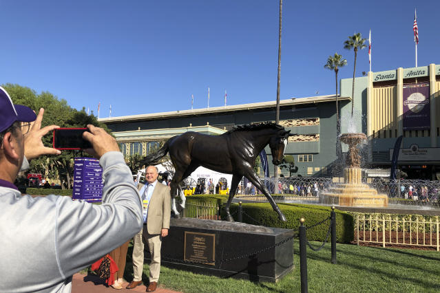 Fans pose for a picture in front of the Zenyatta statue at Santa Anita Park, Friday, Nov. 1, 2019, in Arcadia, Calif. It's the 10th anniversary of the superstar Mare's victory in the Breeders' Cup Classic. (AP Photo/Beth Harris)