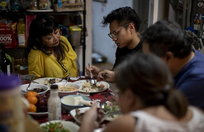 "Justin Foronda, second from left, has dinner with his mother, Lina, left, brother Anthony and Anthony's girlfriend Michelle Diaz. When the coronavirus crisis began, Foronda, a nurse at Sherman Oaks Hospital, took on extra shifts. About 18% of registered nurses in California are of Philippine descent, according to a 2016 survey. <span class=""copyright"">(Gina Ferazzi / Los Angeles Times)</span>"