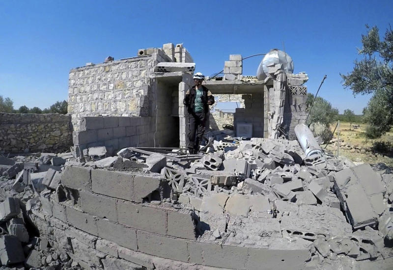 This photo provided by the Syrian Civil Defense White Helmets, shows a Civil Defense worker searching for victims from under the rubble of a destroyed building that was hit by airstrikes in the northern town of Maaret al-Numan, in Idlib province, Syria, Thursday, Aug. 22, 2019. Syrian warplanes carried out airstrikes on towns and villages north of Khan Sheikhoun, including the town of Maaret al-Numan, according to opposition activists. Maaret al-Numan, like Khan Sheikhoun sits on the highway linking Damascus with the northern city of Aleppo, Syria's largest. (Syrian Civil Defense White Helmets via AP)