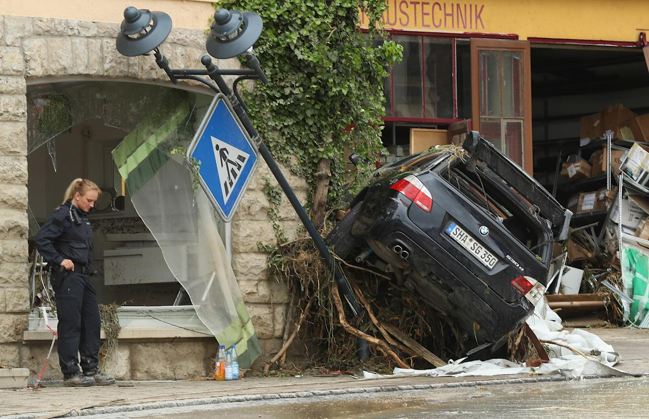 <p>A policewoman stands near a car smashed against a building on May 30, 2016, following a ferocious flash flood the night before in Braunsbach, Germany. (Sean Gallup/Getty Images) </p>