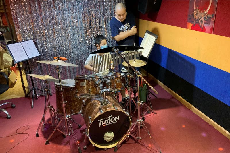 """Dong Jun, drummer of a rock band """"Zhong-D-Yin"""", conducts a drum lesson for a student at a studio in Shenzhen"""