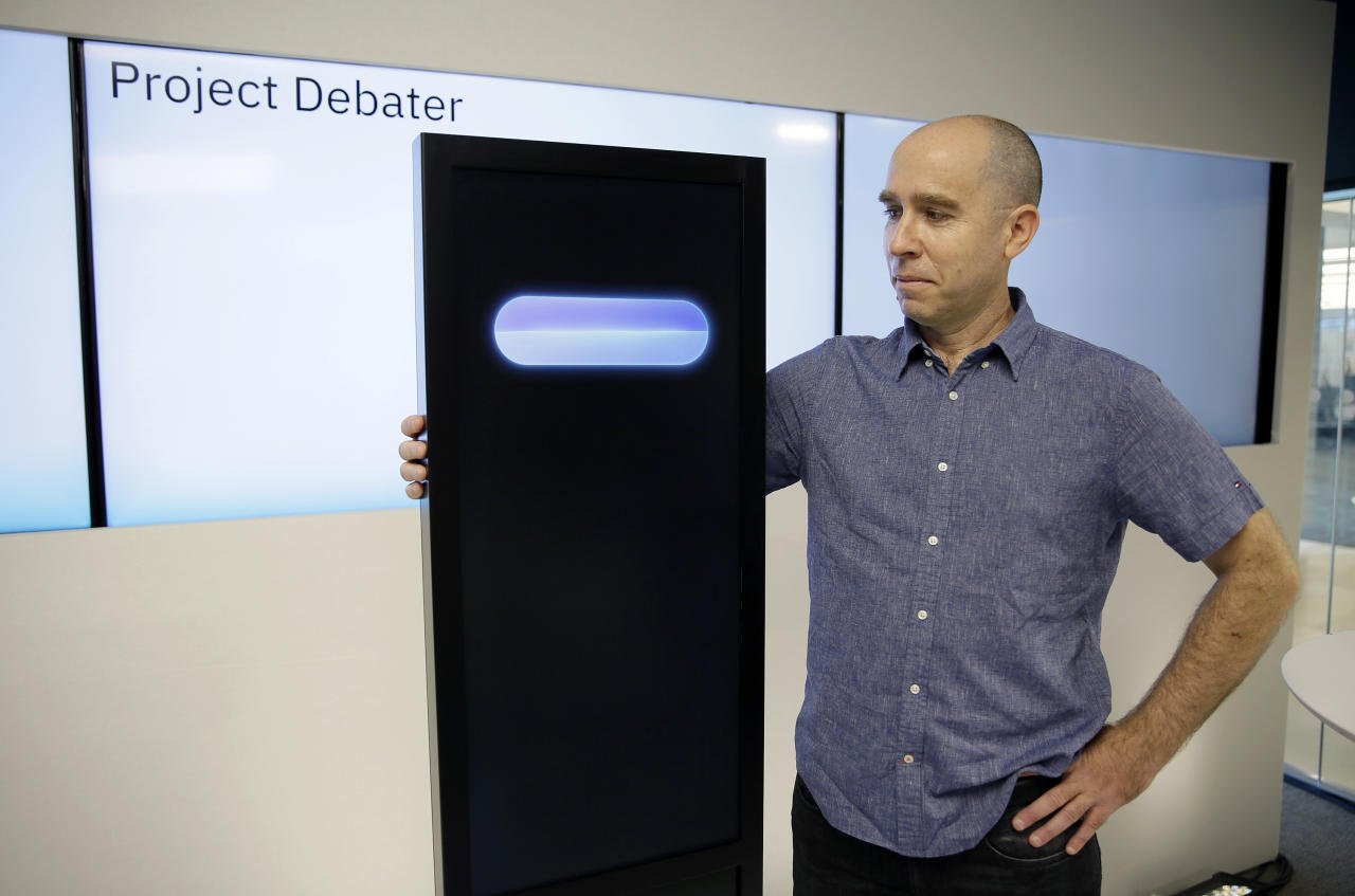 Dr. Noam Slonim, principal investigator, stands with the IBM Project Debater before a debate between the computer and two human debaters Monday, June 18, 2018, in San Francisco. IBM on Monday will pit a computer against two human debaters in the first public demonstration of artificial intelligence technology it's been working on for more than five years. The system, called Project Debater, is designed to be able to listen to an argument, then respond in a natural-sounding way, after pulling in evidence it collects from Wikipedia, journals, newspapers and other sources to make its point. (AP Photo/Eric Risberg)