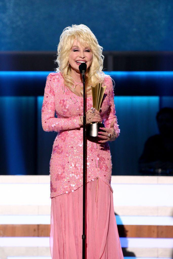 <p>A hue Parton returns to again and again, she always manages to look extra-special in this bubblegum pink. Accepting the Gary Haber Lifting Lives Award from the Academy of Country Music, Dolly exudes Southern charm and beauty in this floral, beaded gown.</p>