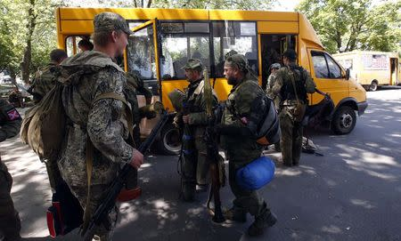 Armed pro-Russian separatists board a bus as they leave their positions in Kramatorsk