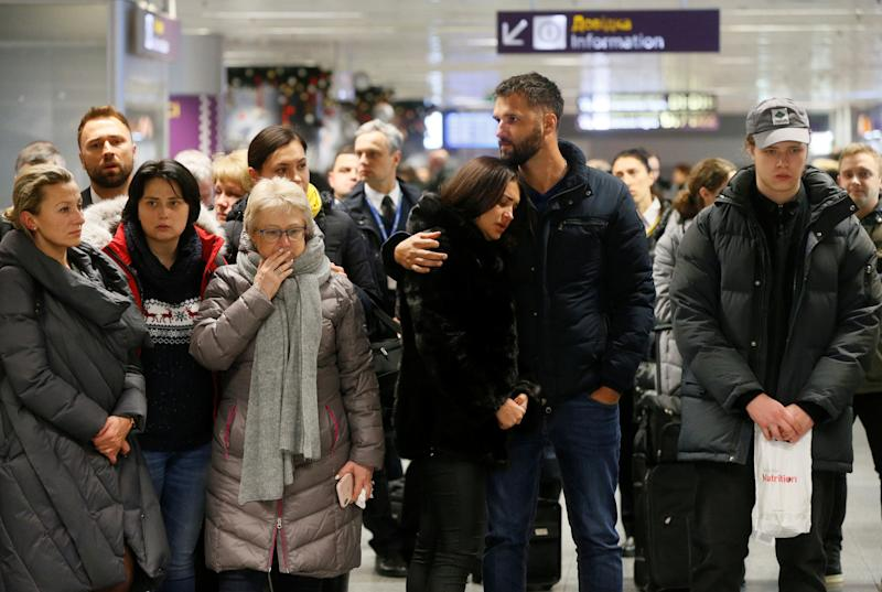 People react in front of a memorial for the flight crew members of the Ukraine International Airlines Boeing 737-800plane that crashed in Iran, at the Boryspil International airport outside Kiev, Ukraine January 8, 2020. REUTERS/Valentyn Ogirenko