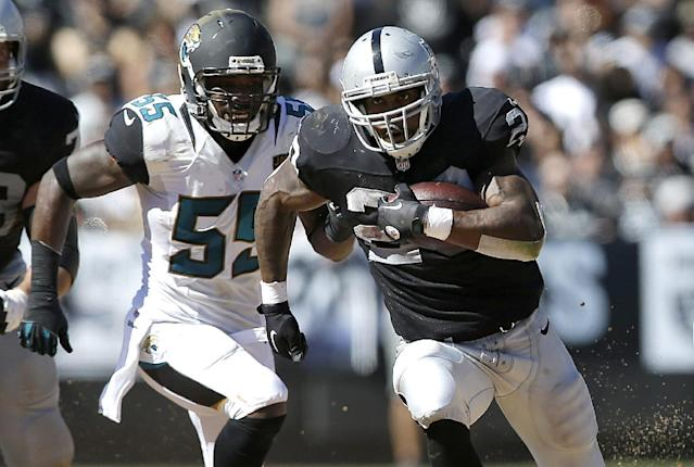 Oakland Raiders running back Darren McFadden runs in front of Jacksonville Jaguars outside linebacker Geno Hayes (55) during the third quarter of an NFL football game in Oakland, Calif., Sunday, Sept. 15, 2013. (AP Photo/Marcio Jose Sanchez)