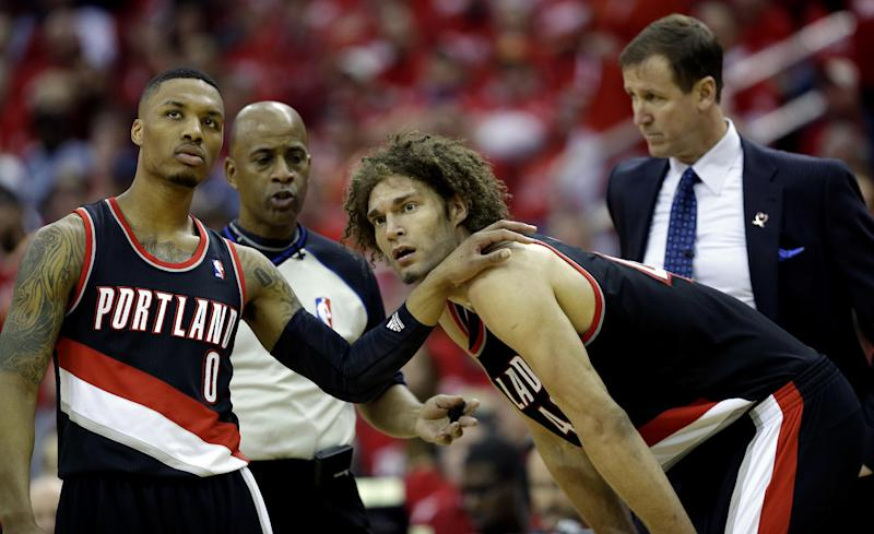 Portland Trail Blazers' Damian Lillard (0) puts his hand on the shoulder of Robin Lopez after Lopez was called for a technical foul against the Houston Rockets during the fourth quarter in Game 1 of an opening-round NBA basketball playoff series Sunday, April 20, 2014, in Houston. The Trail Blazers won 122-120 in overtime. (AP Photo/David J. Phillip)
