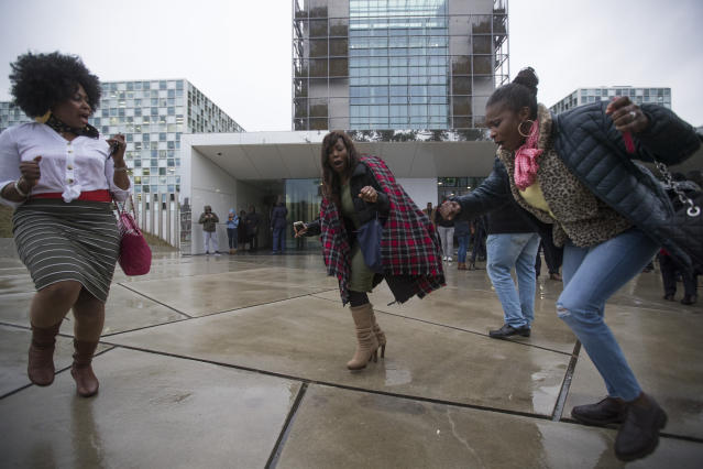 Supporters of former Ivory Coast President Laurent Gbagbo celebrate outside the International Criminal Court, rear, in The Hague, Netherlands, Wednesday, Jan. 16, 2019, after judges ruled that former Ivory Coast President Laurent Gbagbo and a former government minister should be released immediately following their acquittal on charges of involvement in deadly post-election violence in 2010. (AP Photo/Peter Dejong)