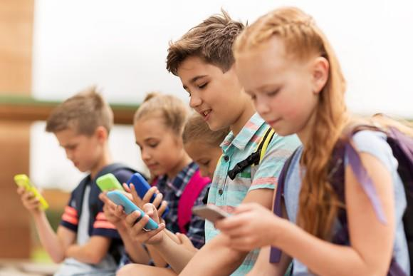 A group of children sitting together, each staring at their own smartphone.
