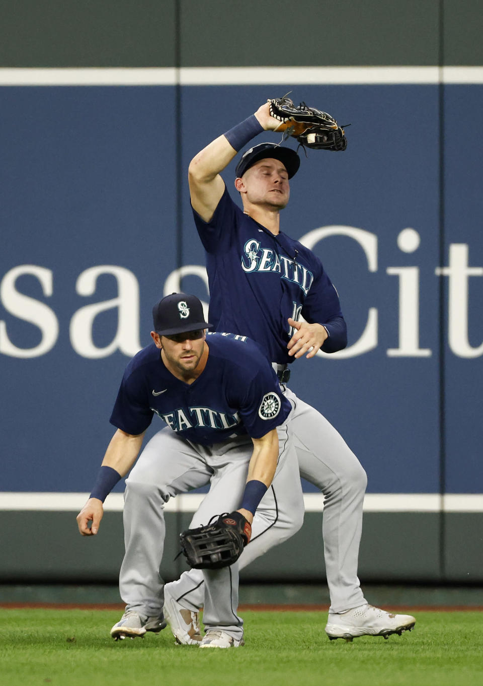 Seattle Mariners center fielder Jarred Kelenic, top, catches a fly ball from Kansas City Royals' Andrew Benintendi as right fielder Mitch Haniger, bottom, avoids the play during the third inning of a baseball game at Kauffman Stadium in Kansas City, Mo., Saturday, Sept. 18, 2021. (AP Photo/Colin E. Braley)