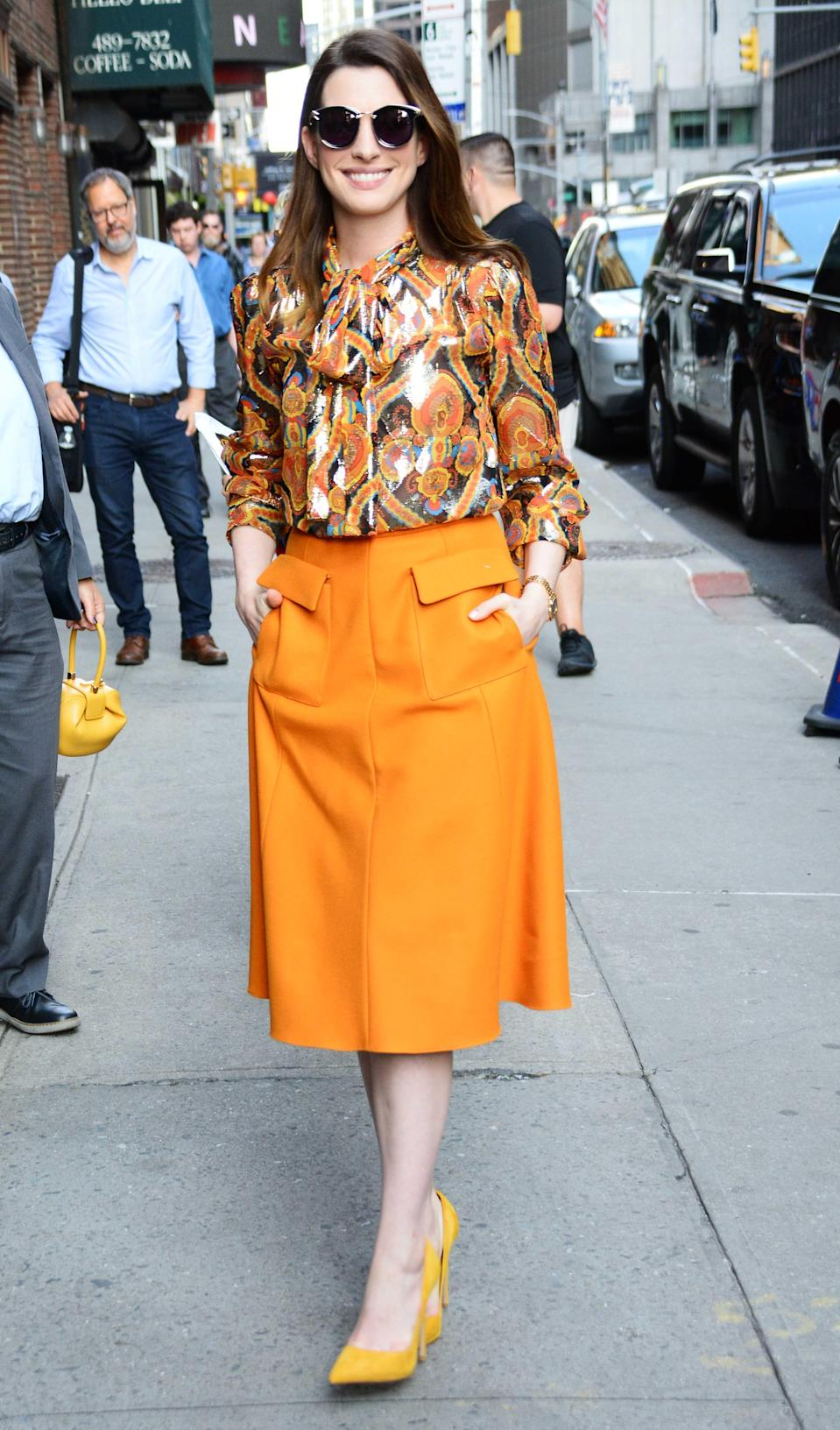 <p>Promoting 'Oceans 8', Anne Hathaway was radiant in a patterned pussy-bow blouse, orange skirt and mathcing heels. <em>[Photo: Getty]</em> </p>