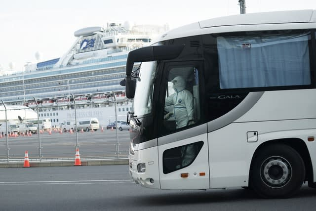 A bus carrying passengers from the quarantined Diamond Princess cruise ship leaves a port in Yokohama, near Tokyo