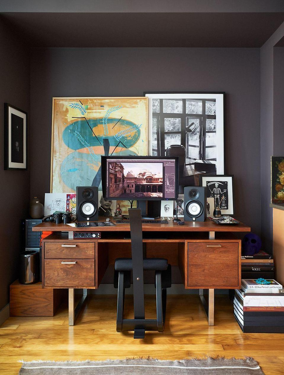 """<p>In photographer <a href=""""https://www.housebeautiful.com/design-inspiration/house-tours/a28071100/bjorn-wallander-manhattan-apartment-tour/"""" rel=""""nofollow noopener"""" target=""""_blank"""" data-ylk=""""slk:Bjorn Wallander's"""" class=""""link rapid-noclick-resp"""">Bjorn Wallander's</a> New York City apartment, the work nook balances a moody espresso backdrop with bright bursts in the artwork and books for inspiration. And don't forget to add speakers (with your housemates' permission, of course).</p>"""