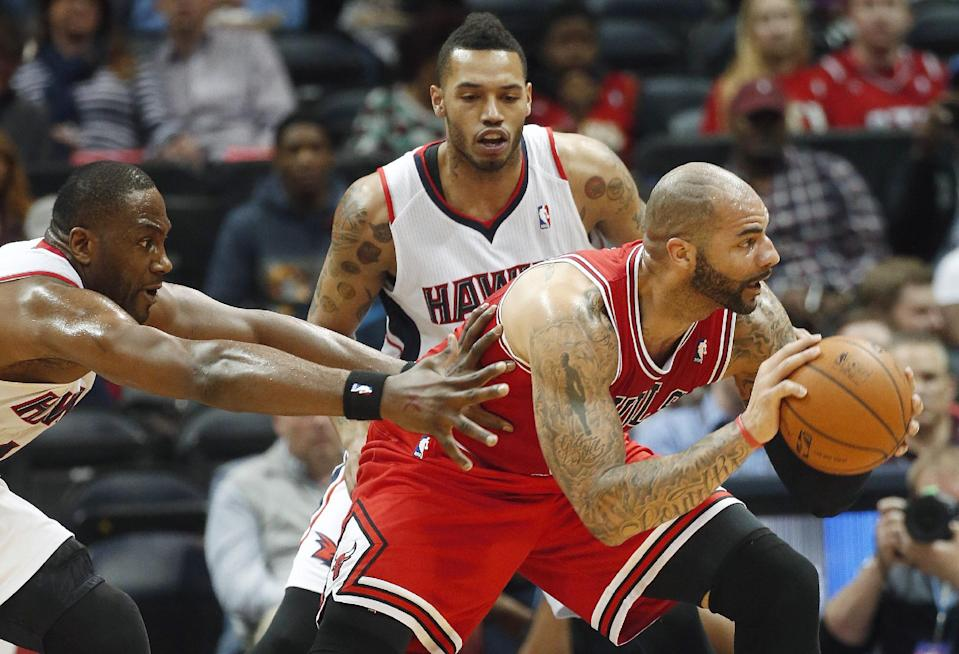 Chicago Bulls power forward Carlos Boozer (5) is defended by Atlanta Hawks' Elton Brand, left, and Mike Scott, in the first half of an NBA basketball game Tuesday, Feb. 25, 2014, in Atlanta. (AP Photo/John Bazemore)