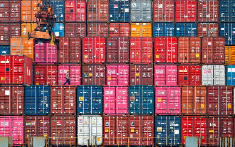 FILE PHOTO: A worker walks on stacks of containers at the Tanjung Priok port in Jakarta