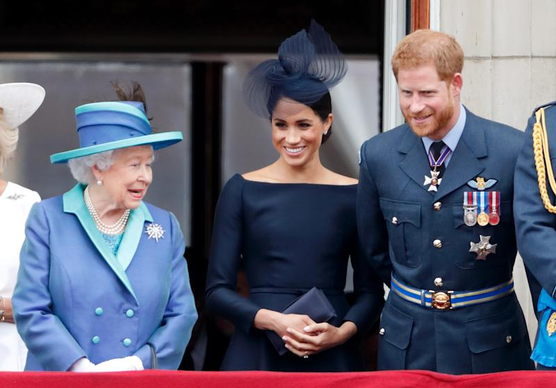LONDON, UNITED KINGDOM - JULY 10: (EMBARGOED FOR PUBLICATION IN UK NEWSPAPERS UNTIL 24 HOURS AFTER CREATE DATE AND TIME) Queen Elizabeth II, Meghan, Duchess of Sussex and Prince Harry, Duke of Sussex watch a flypast to mark the centenary of the Royal Air Force from the balcony of Buckingham Palace on July 10, 2018 in London, England. The 100th birthday of the RAF, which was founded on on 1 April 1918, was marked with a centenary parade with the presentation of a new Queen's Colour and flypast of 100 aircraft over Buckingham Palace. (Photo by Max Mumby/Indigo/Getty Images)