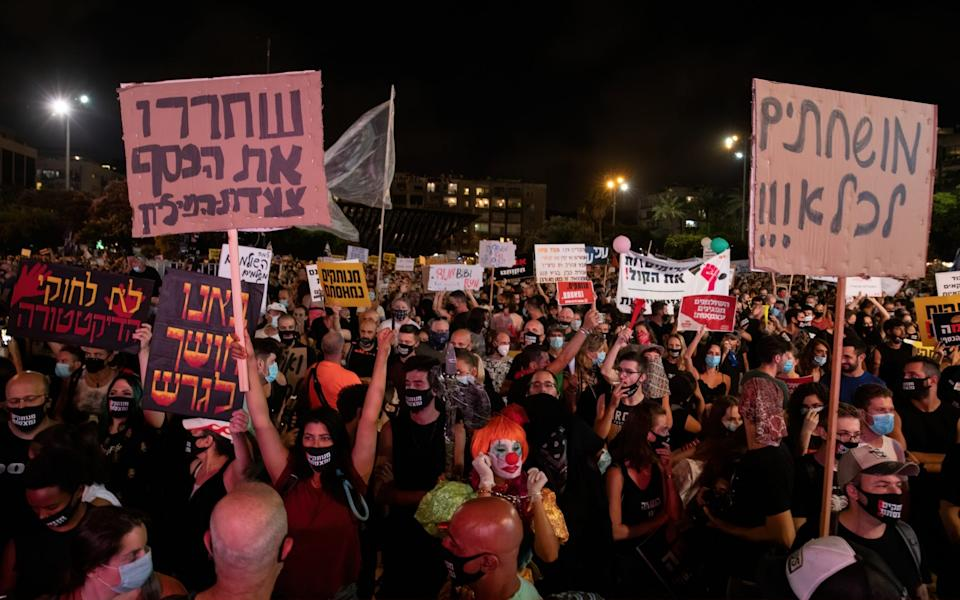 People hold placards during a protest at Rabin square on July 11 - Guy Prives/Getty Images