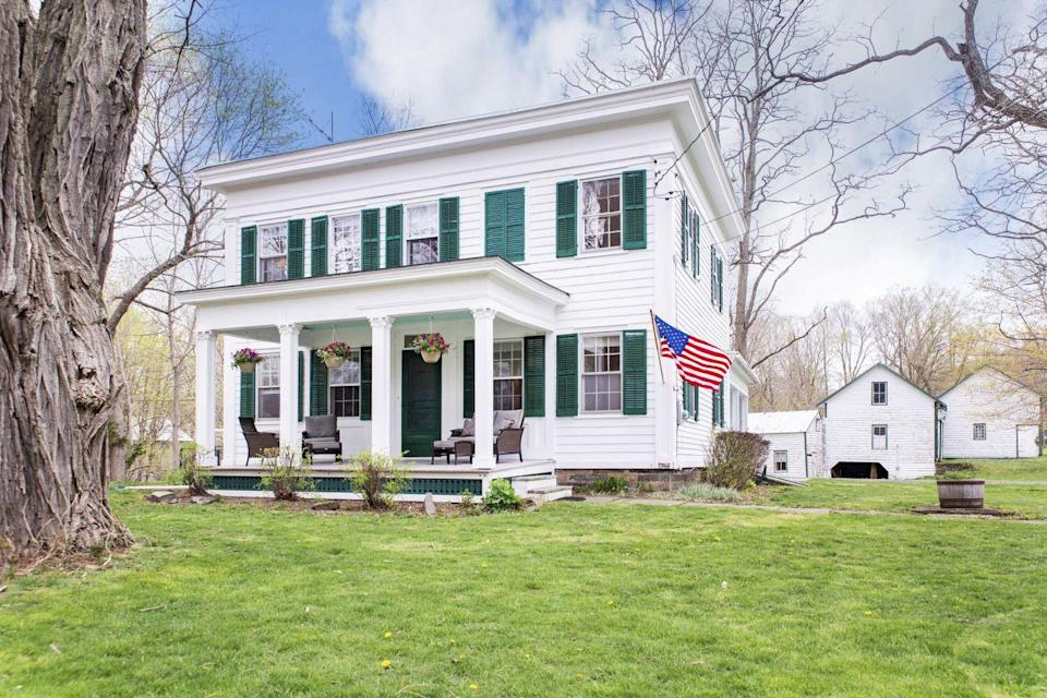 <p>This classic dark green color really doesn't go out of style, especially when painted on a bright white house. </p>
