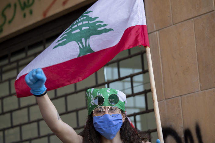 An anti-government protester shouts slogans, while wearing a mask to help curb the spread of the coronavirus, during ongoing protests in front of the Ministry of Economy, in downtown Beirut, in Beirut, Lebanon, Monday, May 18, 2020. (AP Photo/Hassan Ammar)