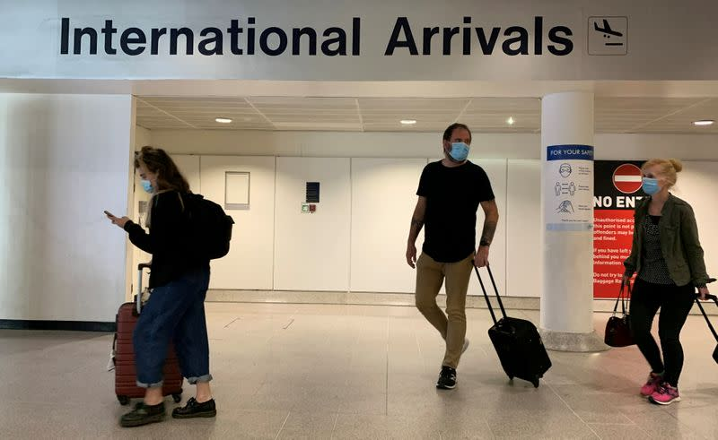 Passengers are seen wearing face coverings after arriving at Manchester Airport following the outbreak of the coronavirus disease (COVID-19) in Manchester, Britain