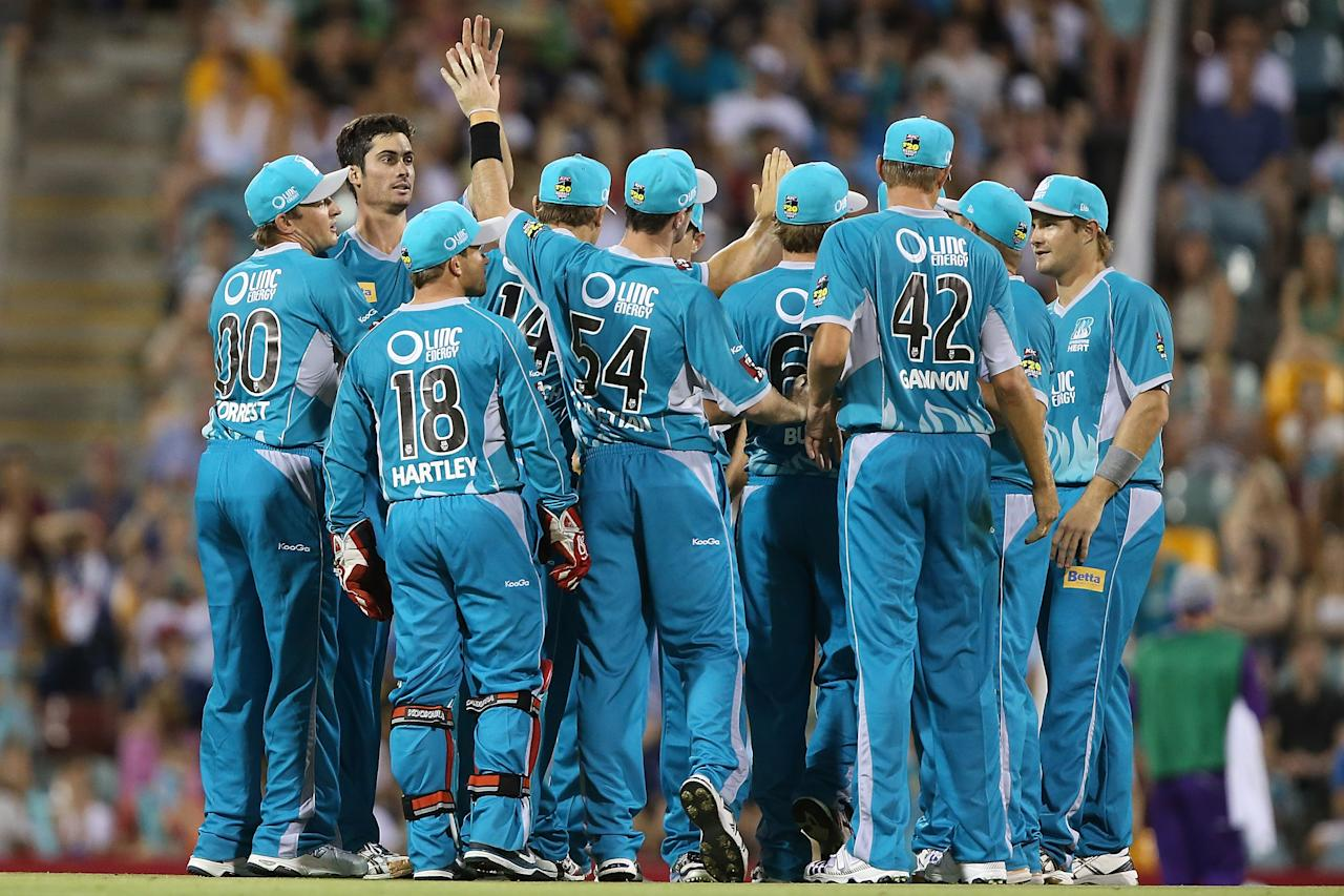 BRISBANE, AUSTRALIA - DECEMBER 09:  Ben Cutting of the Heat celebrates with team mates after dismissing Jon Wells of the Hurricanes during the Big Bash League match between the Brisbane Heat and the Hobart Hurricanes at The Gabba on December 9, 2012 in Brisbane, Australia.  (Photo by Chris Hyde/Getty Images)