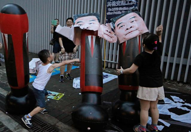 <p>Children hit cardboard boxes with photos of former Hong Kong Chief Executive Leung Chun-ying as protesters attend the annual pro-democracy protest in Hong Kong, Saturday, July 1, 2017. (Photo: Kin Cheung/AP) </p>