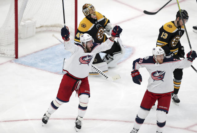 Columbus Blue Jackets center Riley Nash, right, celebrates with Brandon Dubinsky, left, after his goal off Boston Bruins goaltender Tuukka Rask during the third period of Game 1 of an NHL hockey second-round playoff series, Thursday, April 25, 2019, in Boston. Behind Nash is Boston Bruins center Charlie Coyle (13). (AP Photo/Charles Krupa)