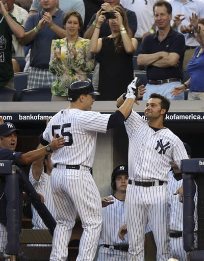 New York Yankees' Russell Martin, left, is greeted by Nick Swisher after hitting a home run during the second inning of the baseball game Monday, July 16, 2012 at Yankee Stadium in New York. (AP Photo/Seth Wenig)