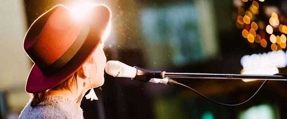 Female singer, performing her vocal sound. With lens flare and spotlight.