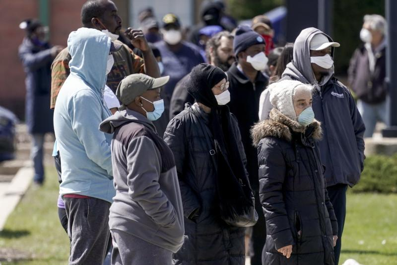 In this May 11, 2020, photo, people line up for a COVID-19 test in a parking lot in Milwaukee. This was one of two sites in the city to open Monday and offer free testing. Wisconsin has been the battleground for political proxy wars for nearly a decade, the backdrop for bruising feuds over labor unions, executive power, redistricting and President Donald Trump. Now, six months before a presidential election, the state is on fire again — some might say still. With a divided state government and a polarized electorate, Wisconsin has emerged as the hot bed of partisan fighting over the coronavirus, including how to slow its spread, restart the seized economy, vote amid a pandemic and judge Trump's leadership. (AP Photo/Morry Gash)