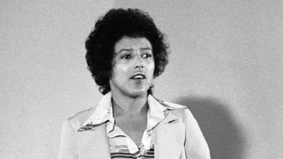 a Black and white photo of a woman named Elaine Brown wearing a soft curly black Afro and a pantsuit with a silk shirt
